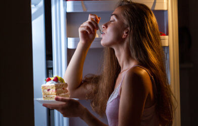 Woman enjoying late night snacking, eating cake in front of refrigerator