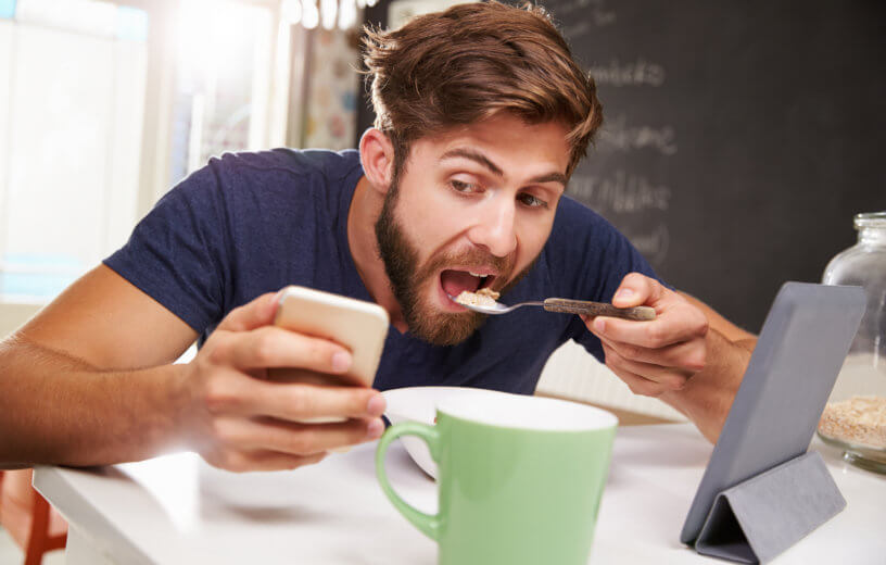 Man eating breakfast while looking at phone, tablet