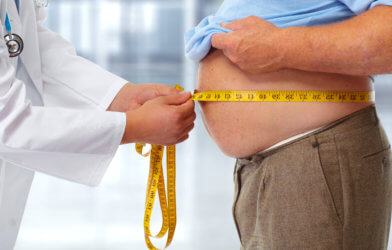 Obesity: Doctor measuring obese man's stomach.