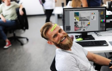 "Office employee with ""Be Happy"" sticker on his head while sitting at desk"