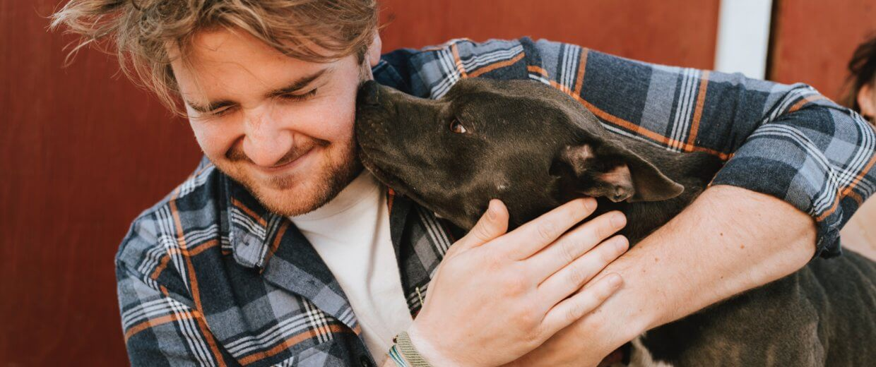 Man getting licked by his dog