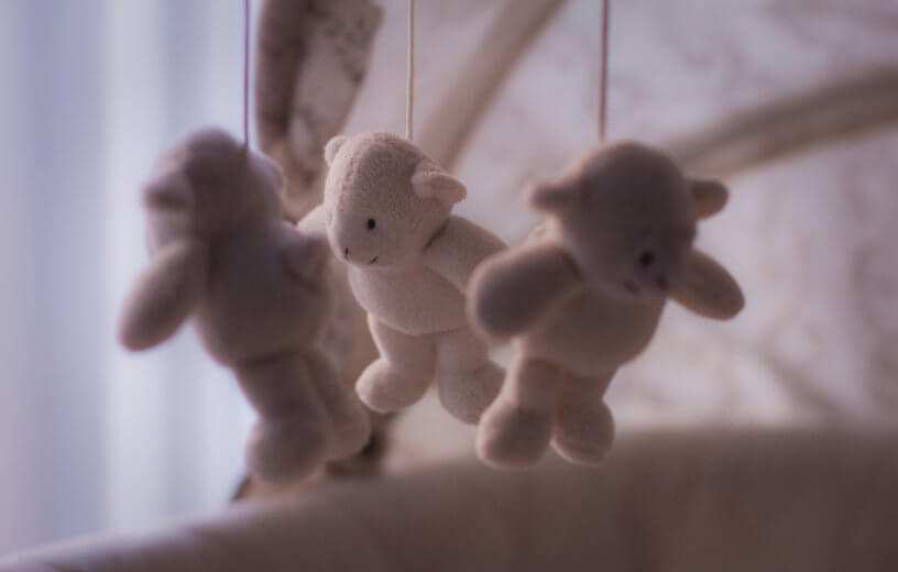 Stuffed bears hanging from baby's crib