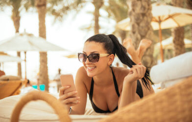 Woman on vacation using phone while lying on a beach