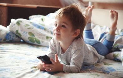 Little boy watching TV in bed