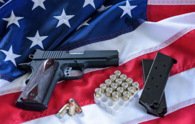 Gun with ammo on an American flag: gun control and gun rights debate