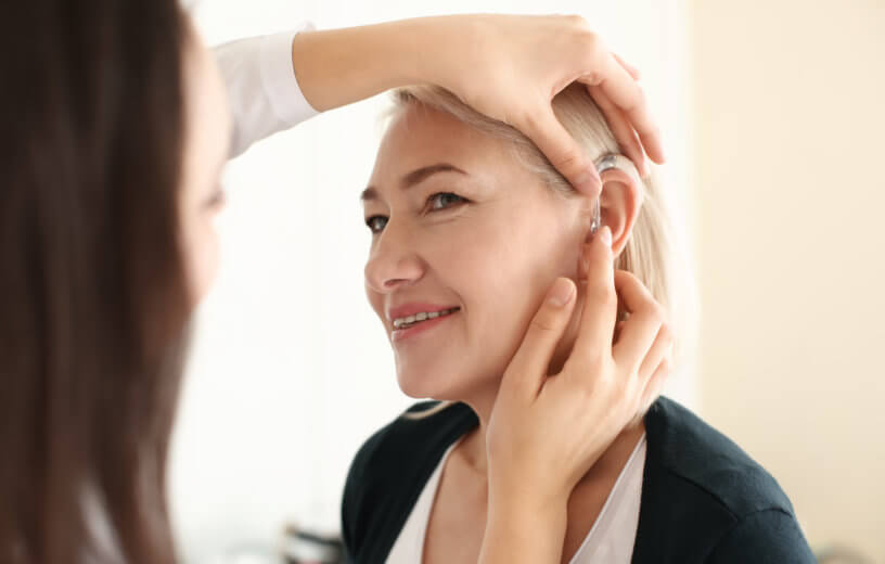 Hearing aid being put in woman's ear