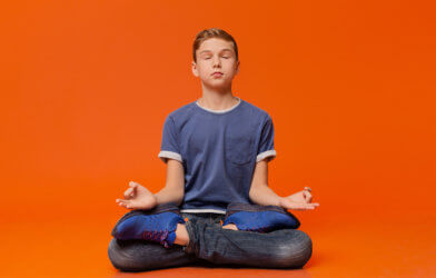 Boy sitting on floor practicing mindfulness meditation