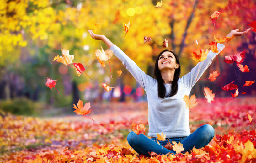 Happy woman throwing autumn leaves in the park