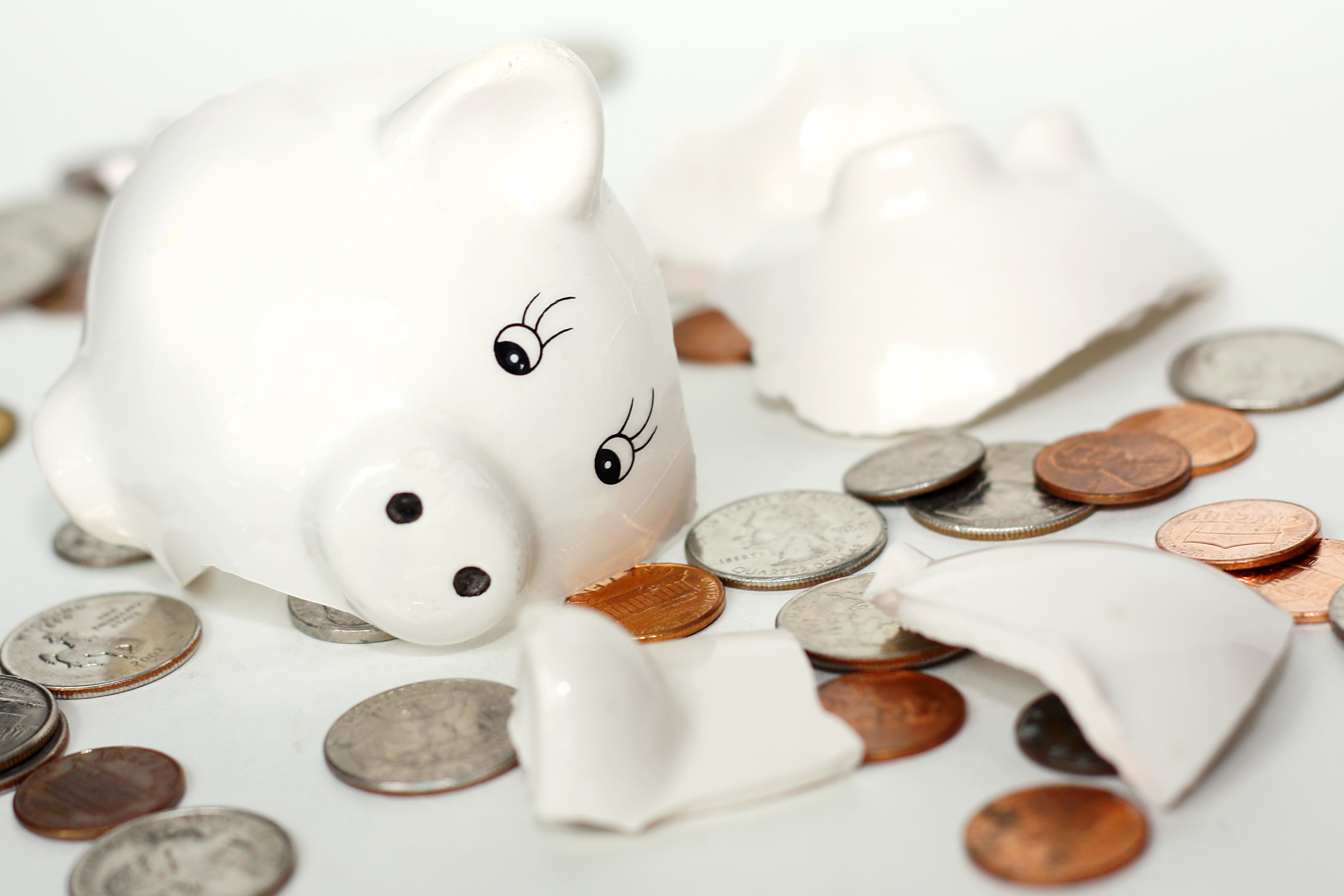 Broken Small Piggy Bank Surrounded By Spilled Coins Study