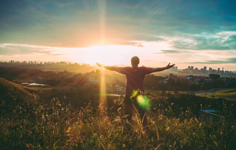 Man filled with awe, arms wide open at sunset