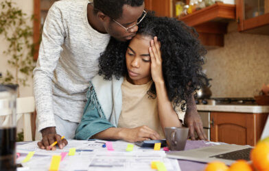 Couple experiencing financial stress while reviewing bills