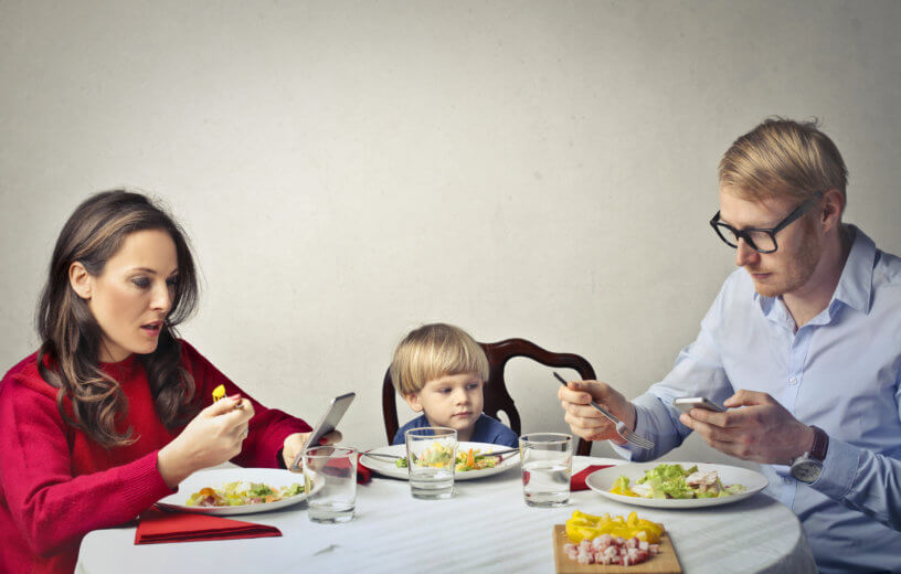 Parents looking at phones while eating dinner