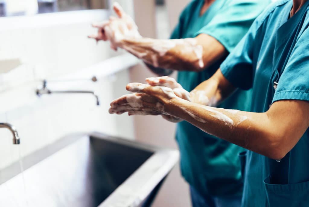 Doctors washing their hands in hospital sink