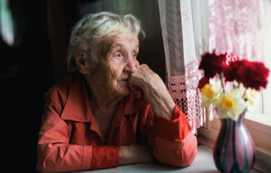 Sad, lonely elderly woman looking out window