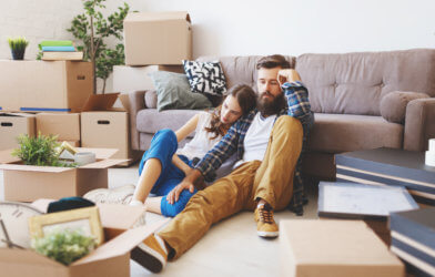 Tired, stressed couple packing boxes while moving