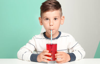 Boy drinking fruit juice or sugary drink in glass