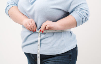 Obese, overweight woman measuring her waist size