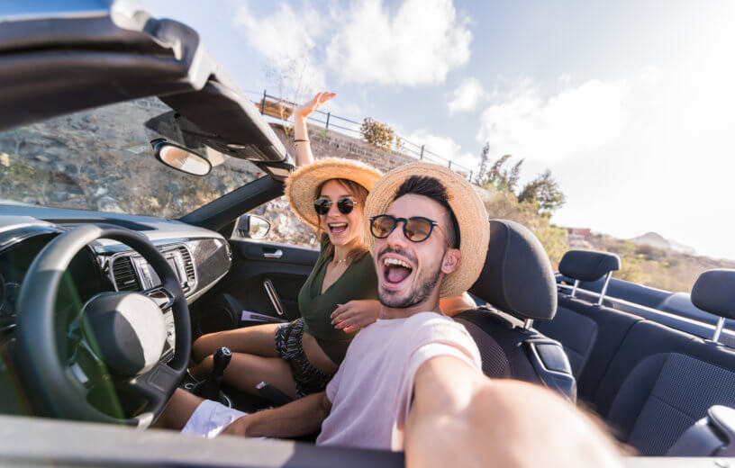 Young couple snapping selfie while driving