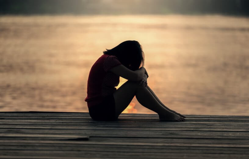 Sad young woman or teen girl alone on pier