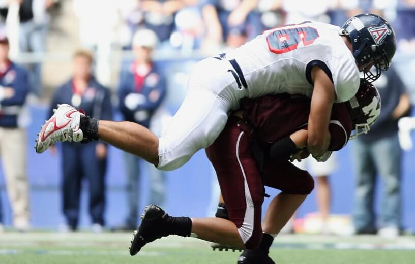 College football quarterback being tackled