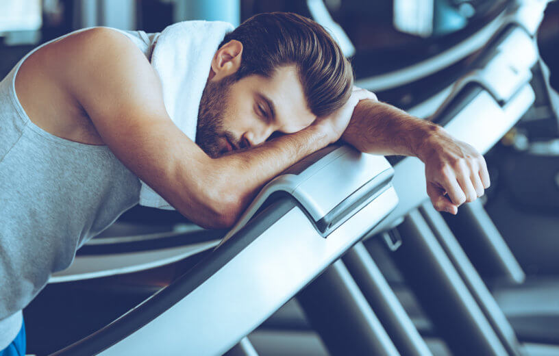 Man on treadmill at gym too tired to run