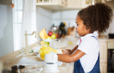 Young child washing dishes, doing chores