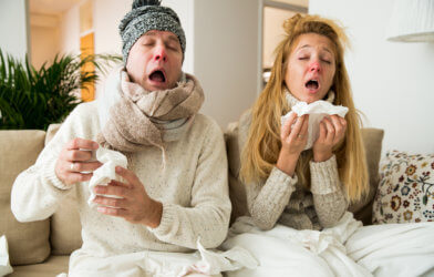 Couple sick at home, sneezing, blowing nose