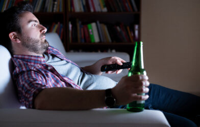 Bored man alone watching TV, drinking beer on couch
