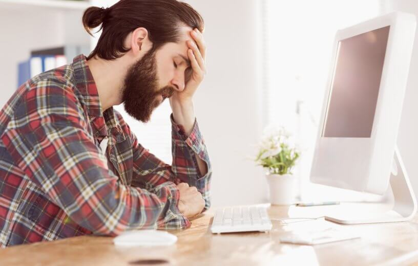 Stressed, upset millennial sitting at work computer