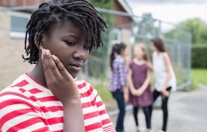 Sad black teen facing bullying, teasing, or racism by peers