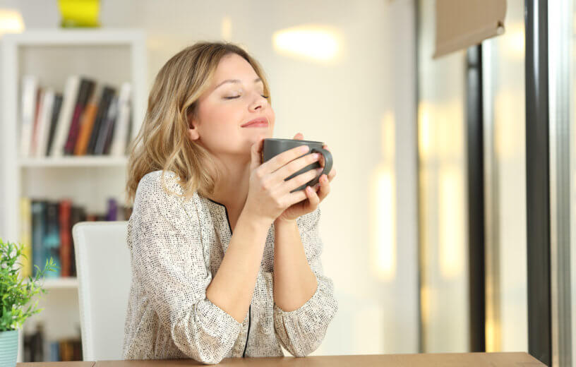 Woman smiling as she drinks a cup of coffee or tea