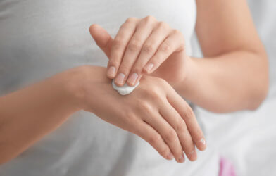 Woman applying hand cream, moisturizer on skin