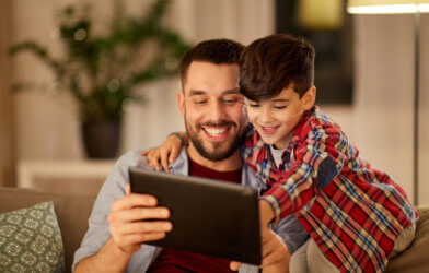 Dad getting help on iPad from young son