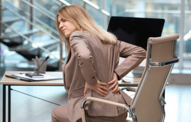 Woman battling lower back pain at office