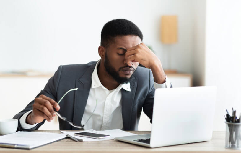 Stressed man at work, suffering from headache at office