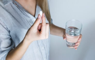 Woman holding pill, glass of water