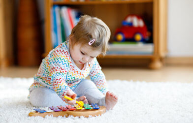Baby girl or toddler playing xylophone