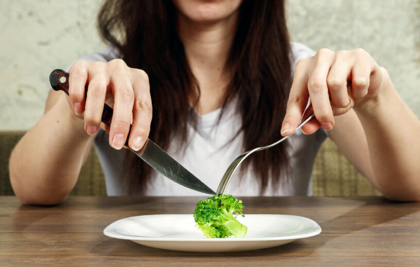 Woman on diet eating broccoli on plate