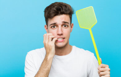 Man with fly swatter appearing nervous