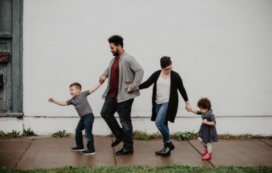Family of four walking on the sidewalk