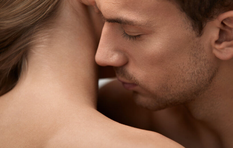 Man kissing or smelling woman's neck while kissing