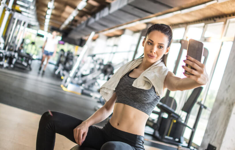 Woman taking selfie while exercising at the gym