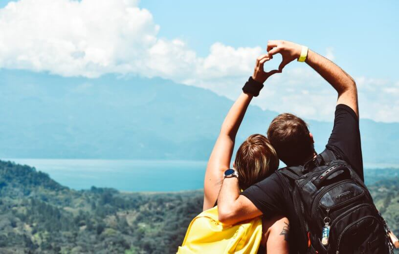 Couple making heart shape with hands on mountain