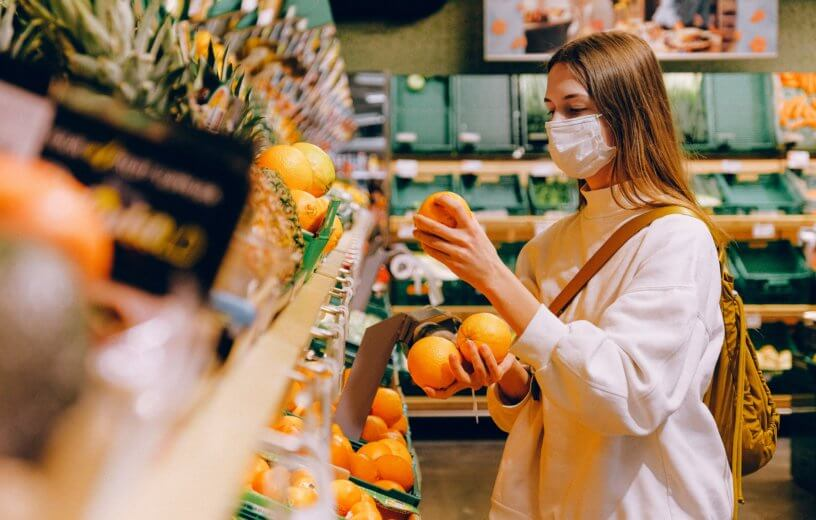 Woman wearing mask while shopping at grocery store during coronavirus outbreak