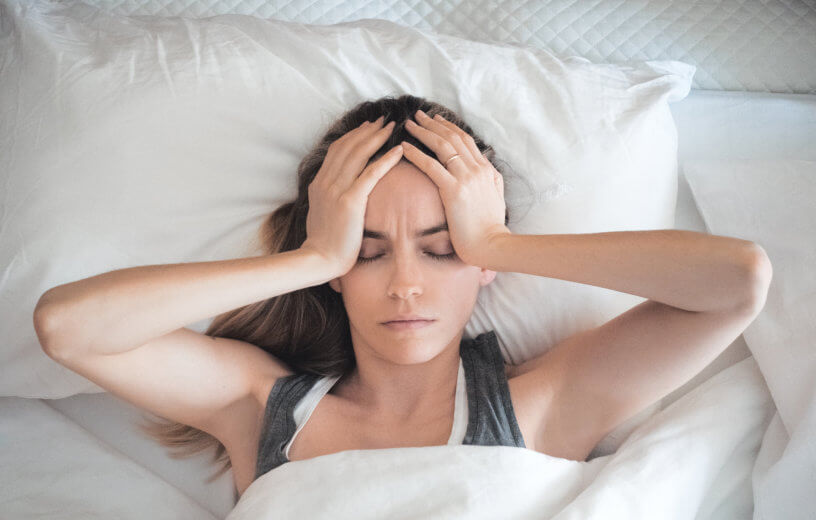 Tired, stressed woman with headache sleeping in bed