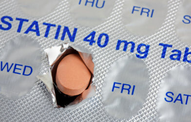 A statin tablet emerging from a marked weekly blister pack