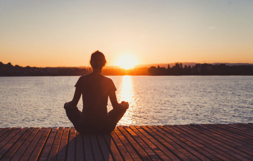 Woman practicing mindfulness meditation at sunset