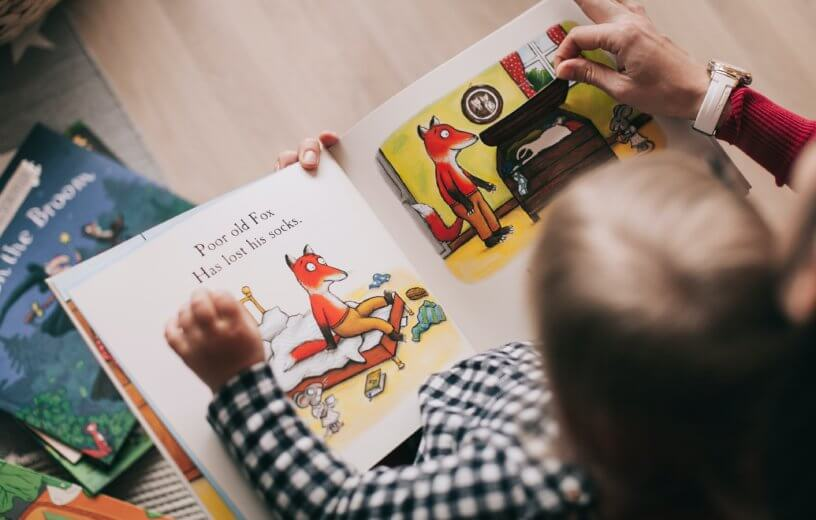 Parent reading book to child