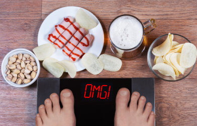 "Weight gain: Scale says ""OMG"" with snacks around it"