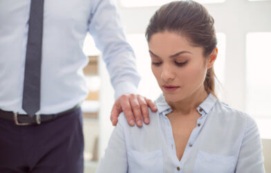 Workplace sexual harassment: Man or boss putting his hand on woman's shoulder